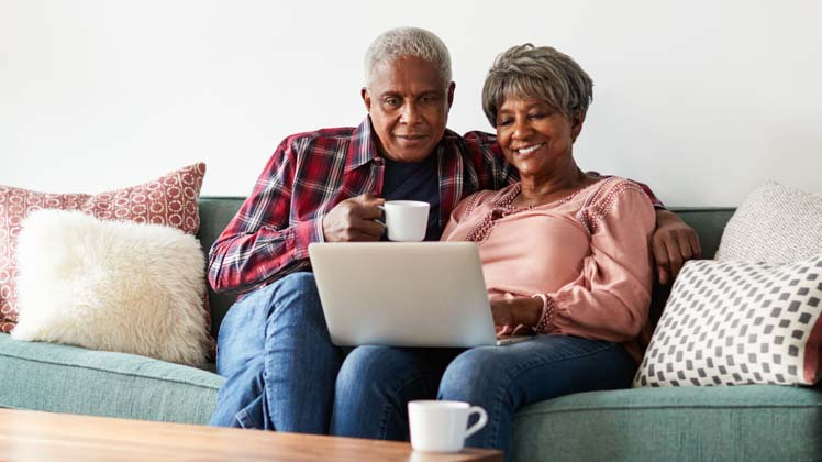 Older African-American couple looking at a computer and drinking coffee